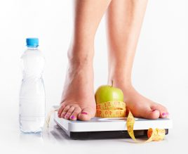 A pair of female feet standing on a bathroom scale with green apple and tape measure between them