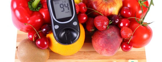 Glucometer with fresh ripe fruits and vegetables on wooden cutting board, concept of diabetes, healthy food, nutrition and strengthening immunity