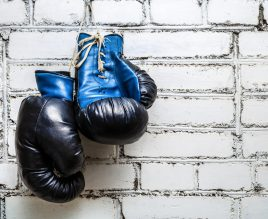 Pair of old blue boxing gloves hanging on white brick wall background.